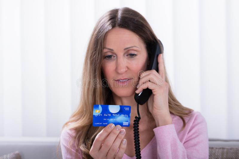Frau, die Kreditkarte bei der Unterhaltung am Telefon hält lizenzfreie stockfotos