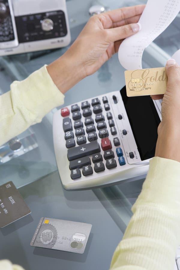 Frau, die Kreditkarte-Gebühren zusammenzählt stockbilder