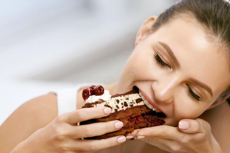 Frau, die Kuchen isst Schöner weiblicher Essennachtisch lizenzfreie stockbilder