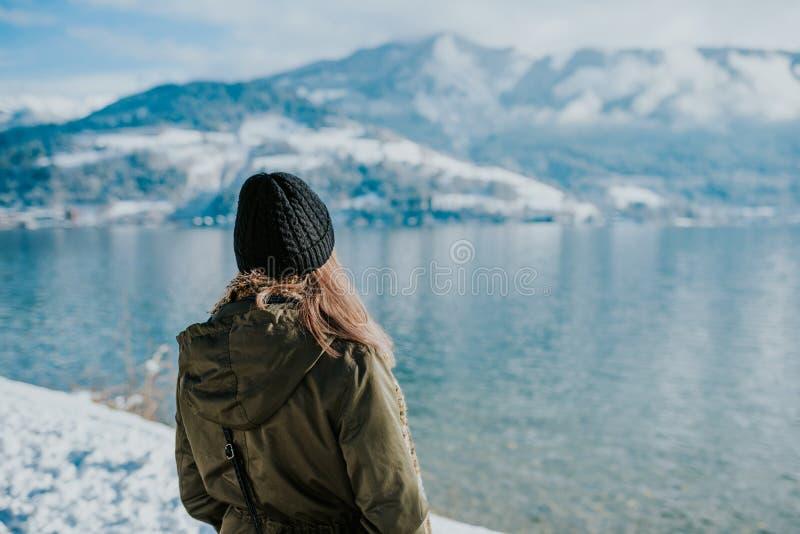 Frau, die lakeshore auf mit schneebedeckten Bergen in der Rückseite steht stockfotografie