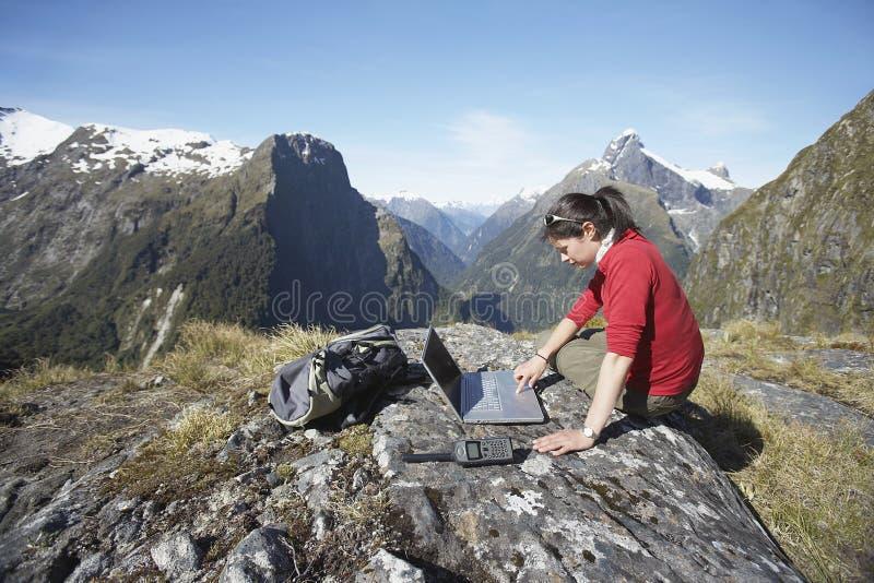 Frau, die Laptop auf Boulder gegen Berge verwendet stockfotos