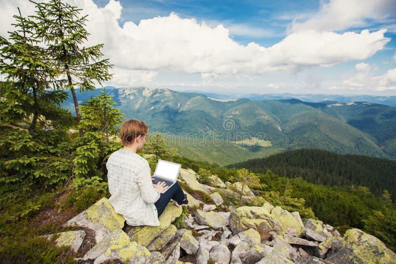 Frau, die an Laptop auf dem Berg arbeitet stockfoto