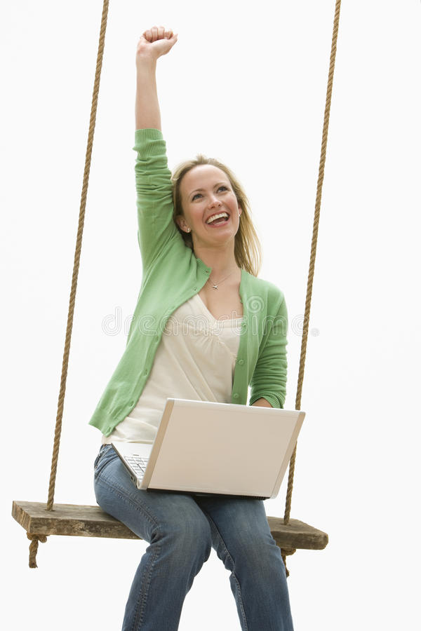Frau, die Laptop auf einem Schwingen verwendet lizenzfreies stockfoto