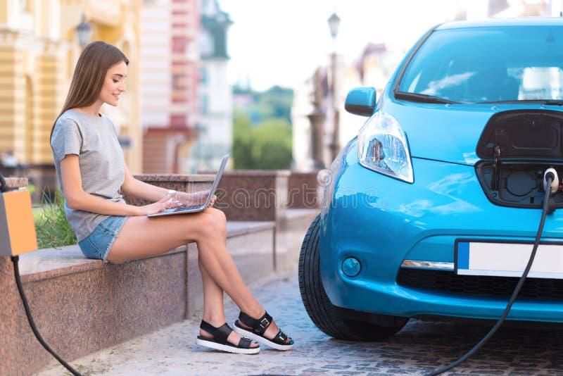 Frau, die Laptop bei der Aufladung des Autos verwendet stockfoto