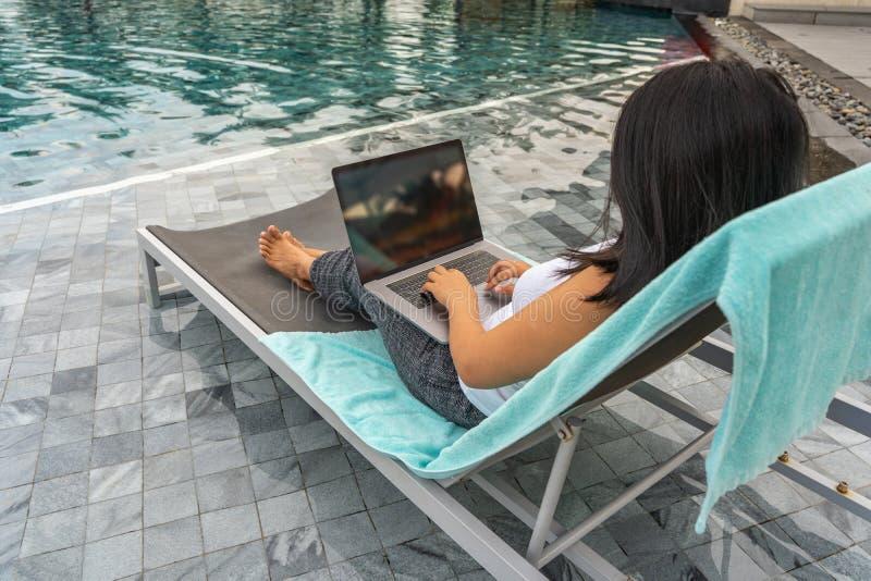 Frau, die Laptop beim Sitzen auf Bank am Swimmingpool verwendet lizenzfreies stockfoto