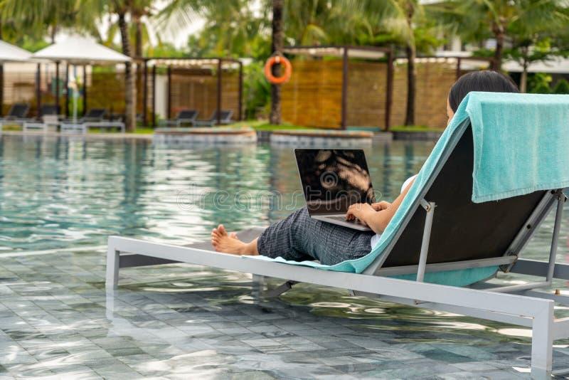 Frau, die Laptop beim Sitzen auf Bank am Swimmingpool verwendet stockfotografie