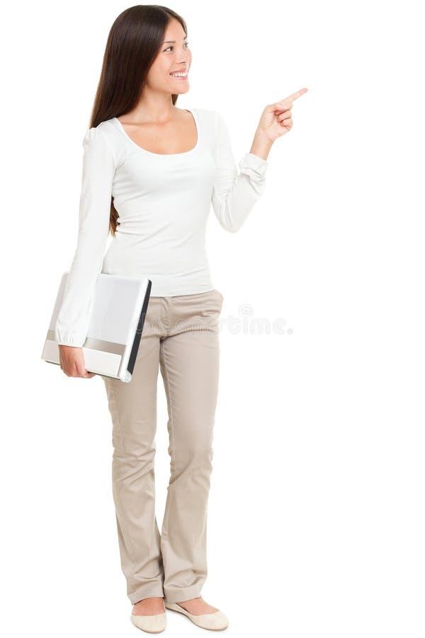 Frau, die Laptop beim Zeigen bei Copyspace hält stockfoto