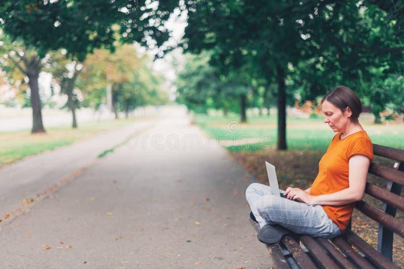 Frau, die Laptop-Computer auf Parkbank verwendet stockfoto
