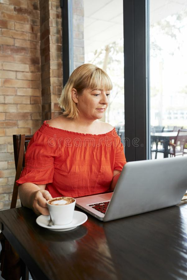Frau, die an Laptop im Café arbeitet lizenzfreie stockbilder