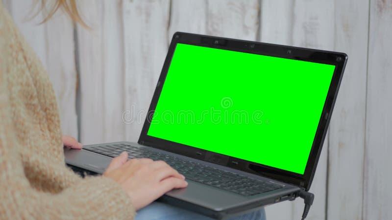 Frau, die Laptop mit grünem Schirm verwendet stockfoto