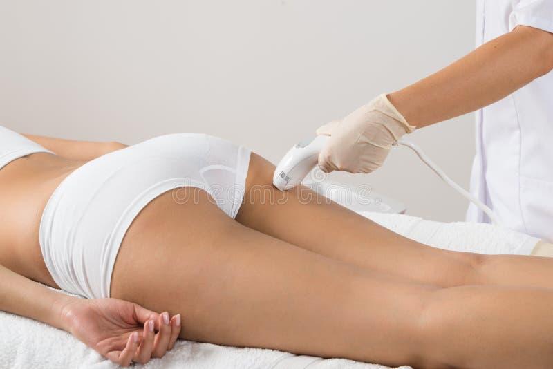 Frau, die Laser-Behandlung auf Hinterteil bekommt lizenzfreies stockfoto