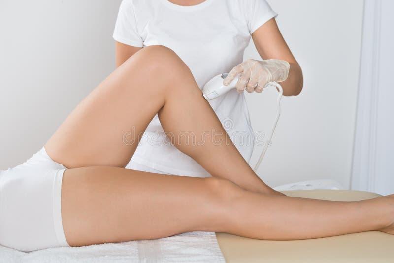 Frau, die Laser-Behandlung auf Schenkel hat stockbilder