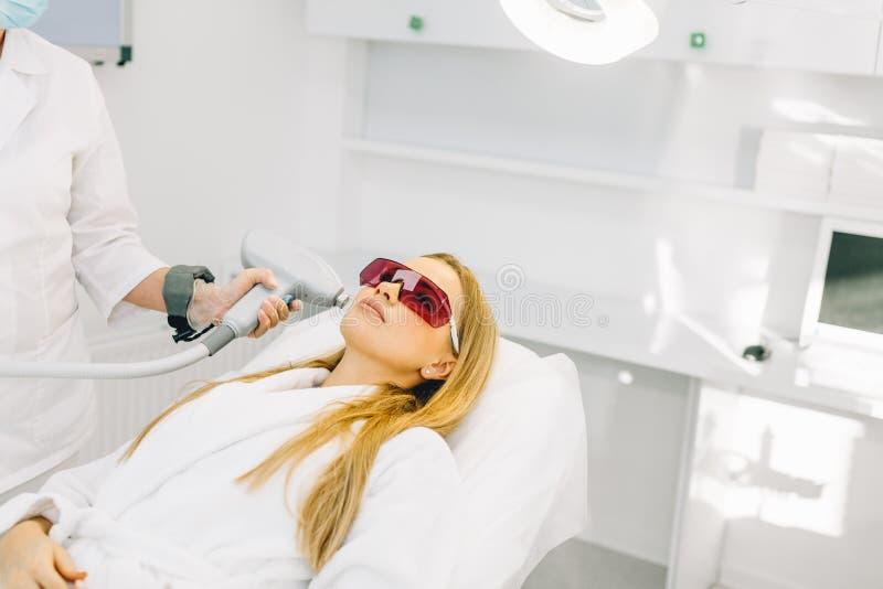 Frau, die Laser und Ultraschallgesichtsbehandlung in der medizinischen Badekurortmitte erhält stockbilder
