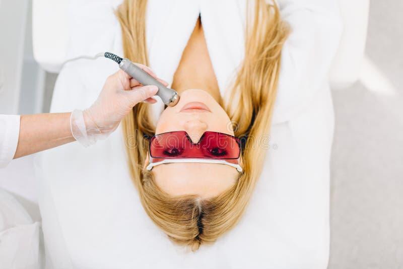 Frau, die Laser und Ultraschallgesichtsbehandlung in der medizinischen Badekurortmitte, Hautverjüngungskonzept erhält stockfotografie