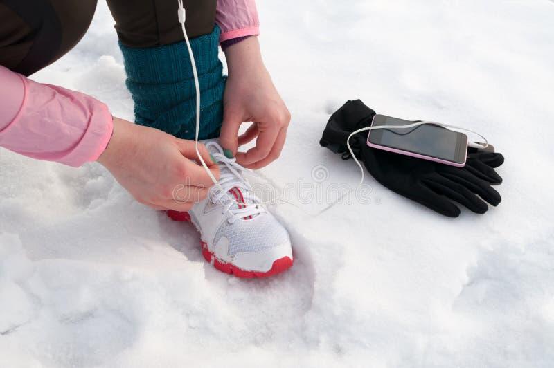 Frau, die Laufschuhe auf Schnee bindet stockbilder