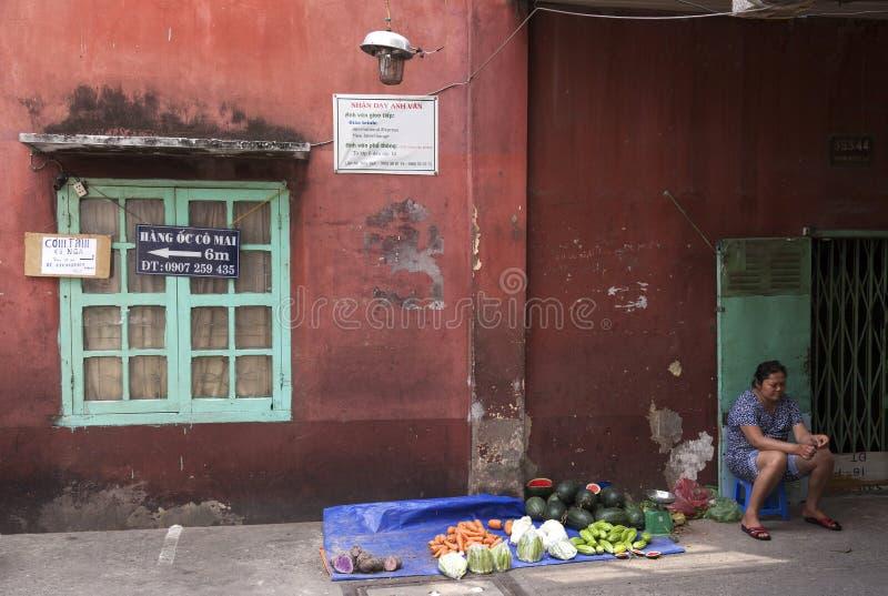 Frau, die Lebensmittel in der Gasse in Saigon verkauft lizenzfreies stockbild