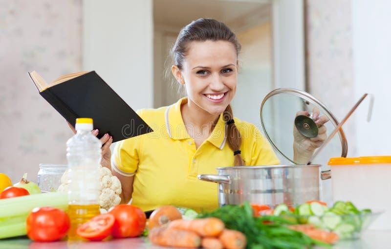 Frau, die Lebensmittel mit Kochbuch kocht lizenzfreie stockfotos