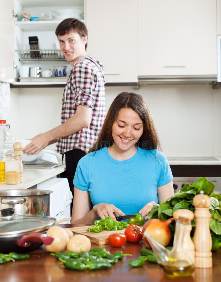 Frau, die Lebensmittel während waschende Teller des Mannes kocht stockfoto
