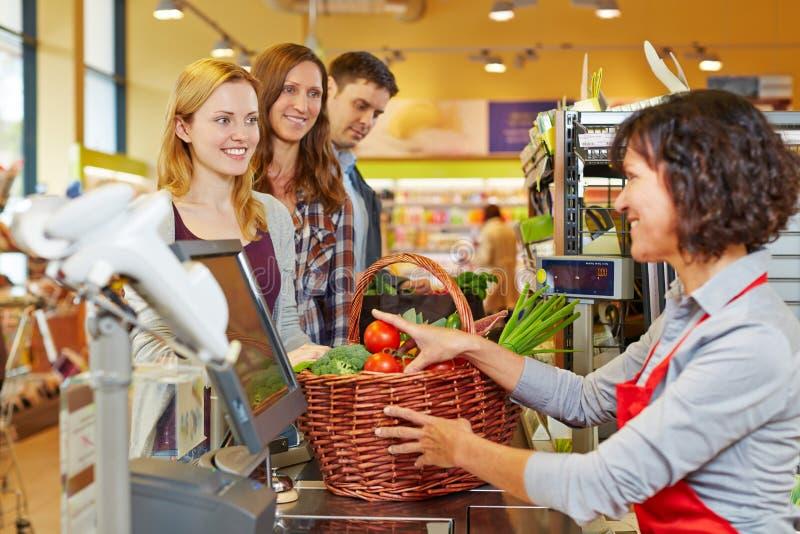 Frau, die Lebensmittelgeschäfte an zahlt stockfoto