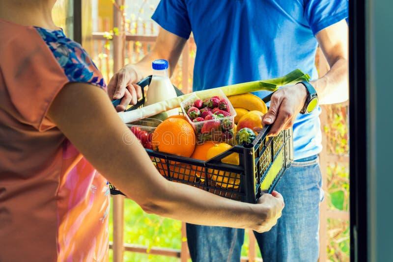 Frau, die Lebensmittelgeschäftkasten vom Lieferer annimmt stockfotografie