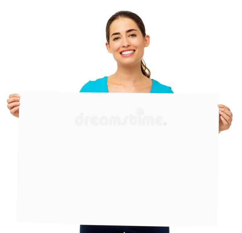 Frau, die leere Anschlagtafel über weißem Hintergrund hält lizenzfreie stockfotos
