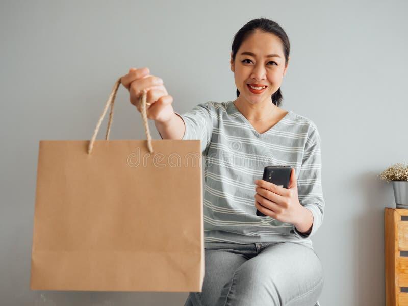 Frau, die leere Papiertüte des Produktes vorführt, das sie online kaufte Konzept des Onlineeinkaufens stockbilder