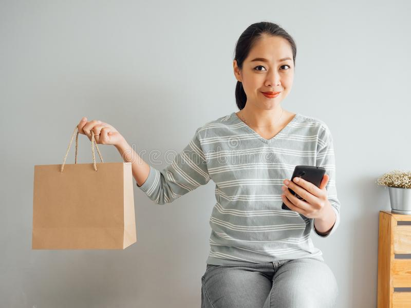 Frau, die leere Papiert?te des Produktes vorf?hrt, das sie online kaufte Konzept des Onlineeinkaufens stockfotografie
