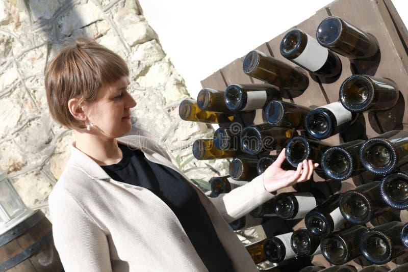 Frau, die leere Weinflasche ber?hrt stockfotos