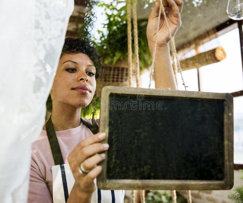 Frau, die leeres Zeichen durch das Glasfenster hängt lizenzfreies stockbild