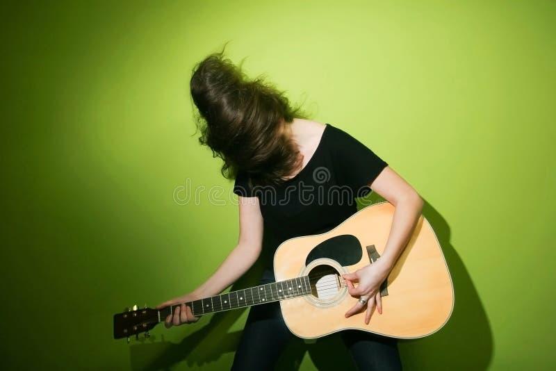 Frau, die leidenschaftlich Gitarre spielt lizenzfreie stockfotografie