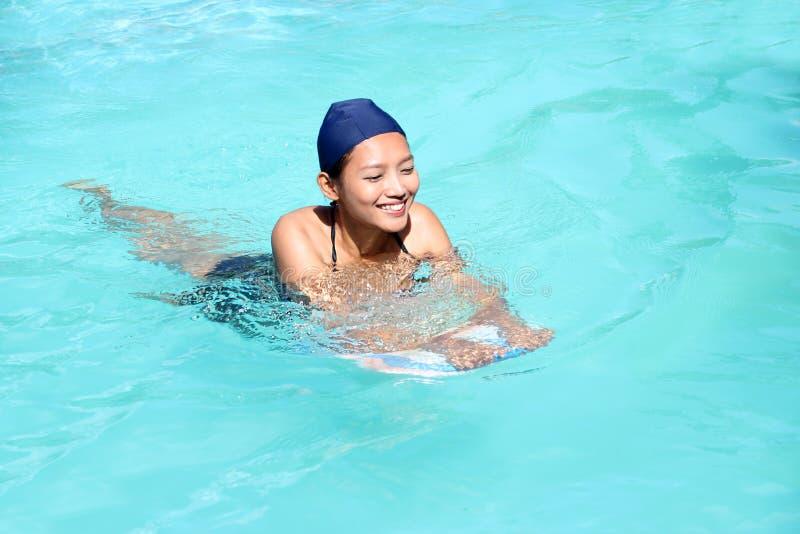 Frau, die lernt, im Pool mit Brett zu schwimmen stockfotos