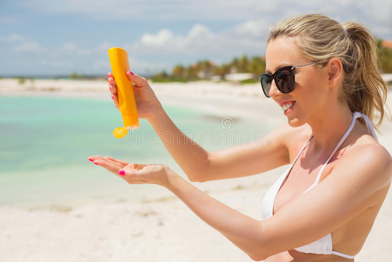 Frau, die Lichtschutz auf dem Strand verwendet stockfotos