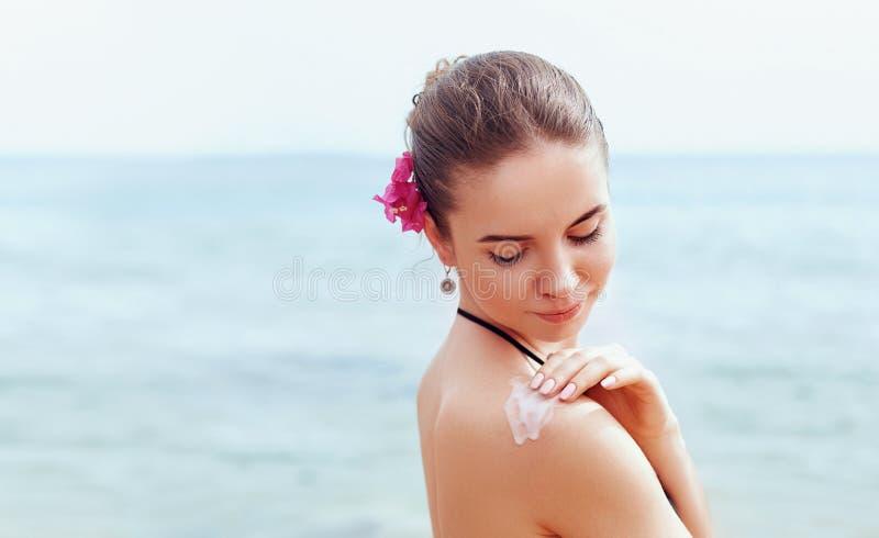 Frau, die Lichtschutzcreme auf gebr?unter Schulter anwendet Skincare K?rper-Sonnenschutzsonnencreme Bikinifrauen-Abstrich befeuch lizenzfreie stockfotografie