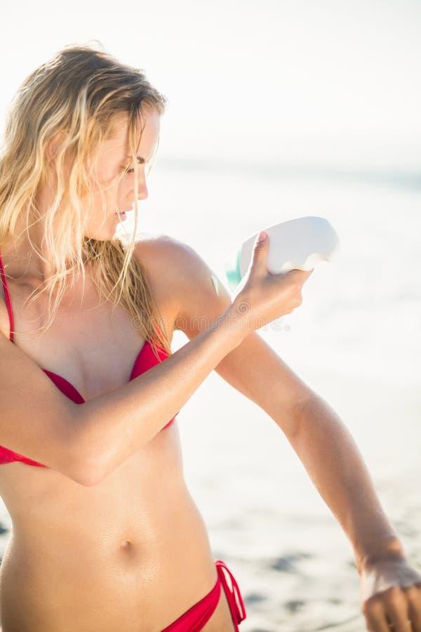 Frau, die Lichtschutzlotion auf dem Strand anwendet stockfotos