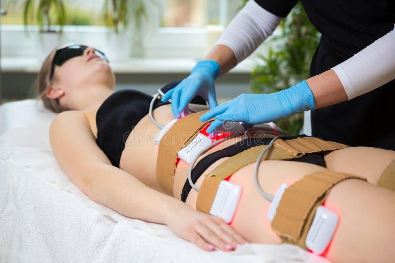 Frau, die lipo Laser-Therapie im Badekurort abnehmend empfängt lizenzfreie stockfotografie