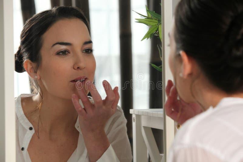 Frau, die Lippenglanz anwendet stockbild