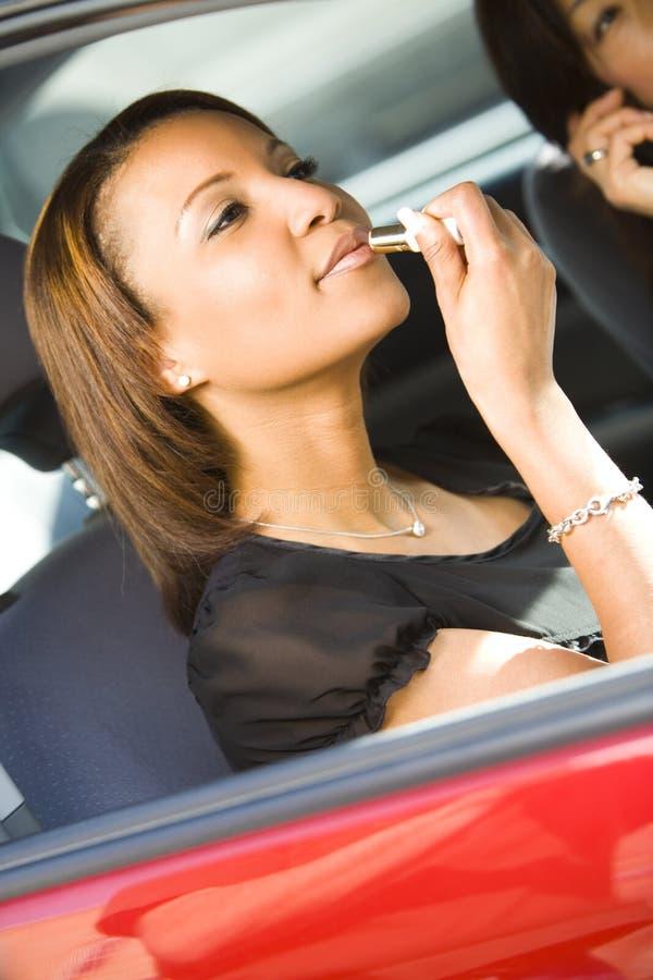 Frau, die Lippenstift im Auto anwendet stockfoto