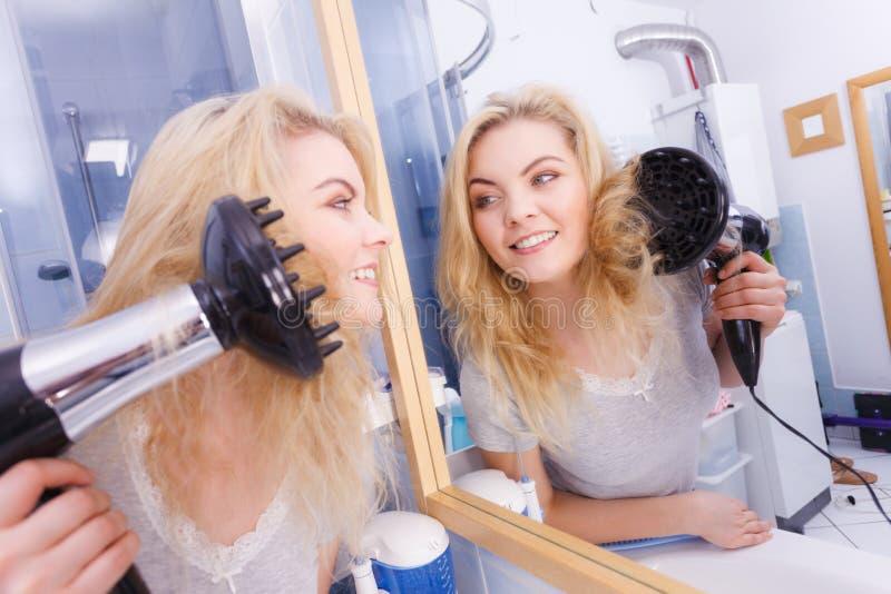 Frau, die Locken mit hairdryer Diffusor tut lizenzfreie stockbilder