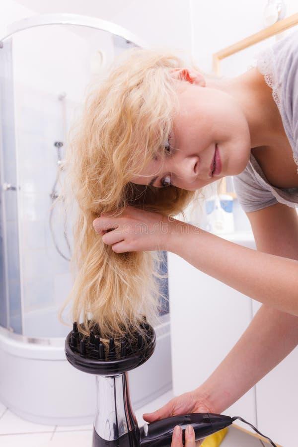 Frau, die Locken mit hairdryer Diffusor tut stockfoto
