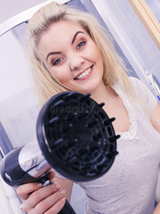 Frau, die Locken mit hairdryer Diffusor tut stockbilder