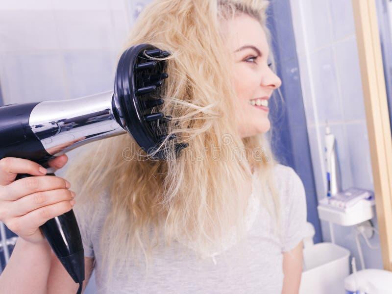 Frau, die Locken mit hairdryer Diffusor tut stockfotografie