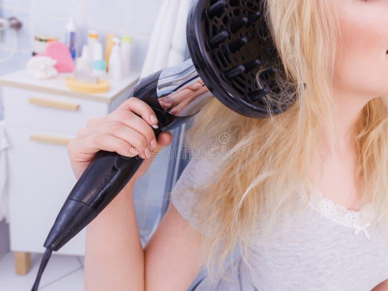 Frau, die Locken mit hairdryer Diffusor tut stockfotos