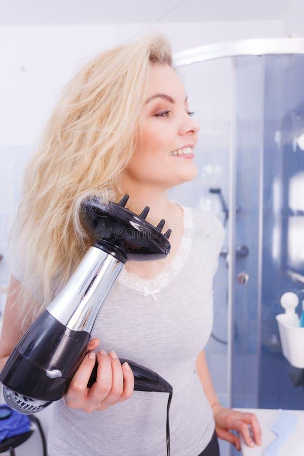 Frau, die Locken mit hairdryer Diffusor tut lizenzfreie stockfotografie