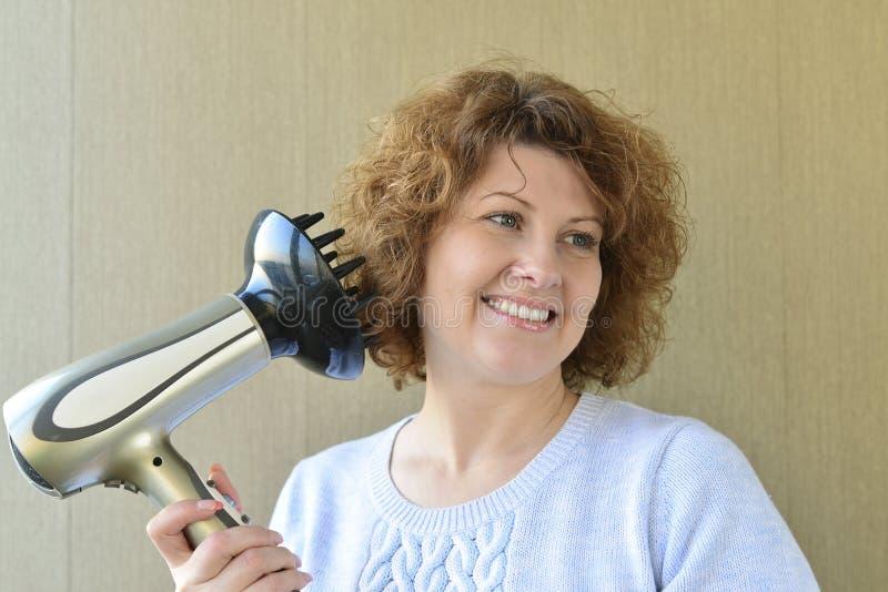 Frau, die Locken mit hairdryer und Diffusor tut lizenzfreies stockfoto