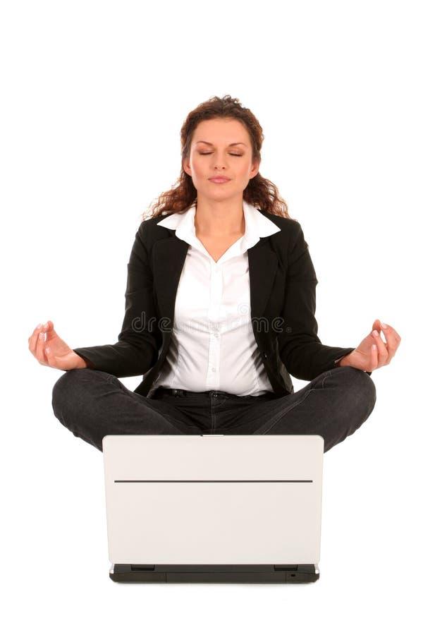 Frau, die in Lotosstellung mit Laptop sitzt lizenzfreie stockfotografie