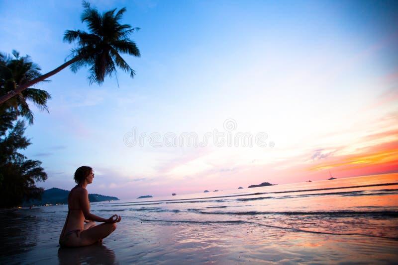 Frau, die Lotosyogahaltung auf dem Strand tut lizenzfreie stockfotos