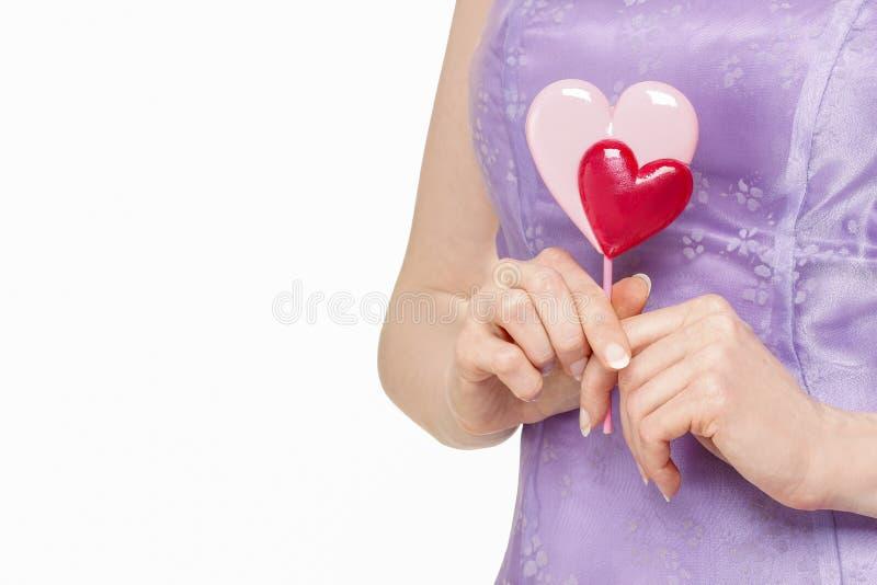 Frau, die Lutscher in der Herzform hält stockbild