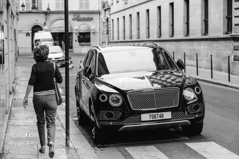Frau, die Luxus-Bentley Bentayga Hybrid SUV bewundert lizenzfreie stockfotos