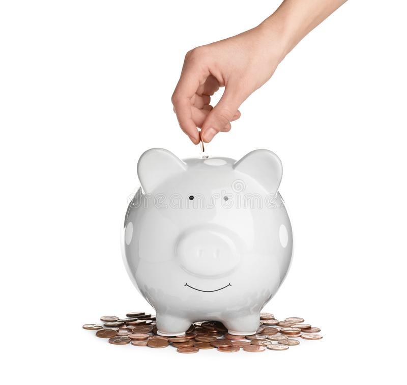 Frau, die Münze in Sparschwein auf weißem Hintergrund setzt lizenzfreie stockfotos