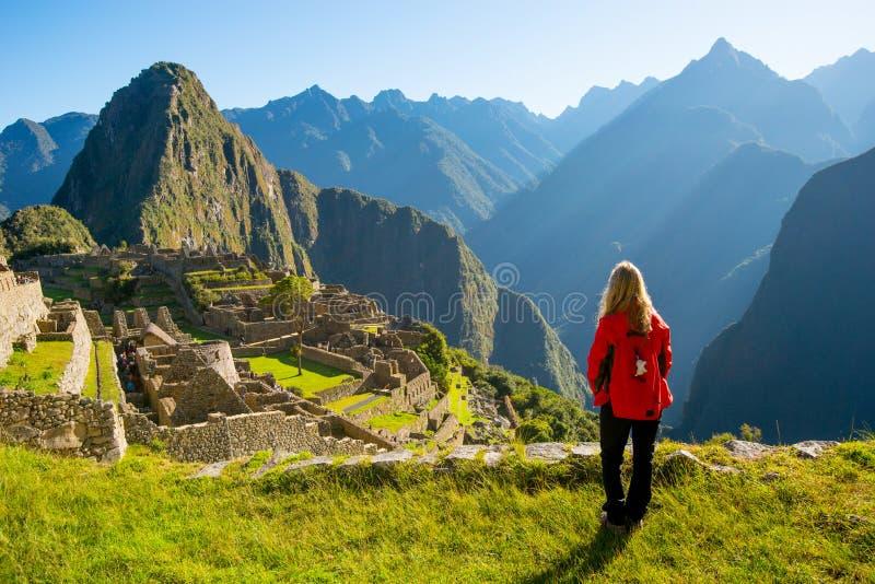 Frau, die Machu Picchu bei Sonnenaufgang betrachtet stockbild